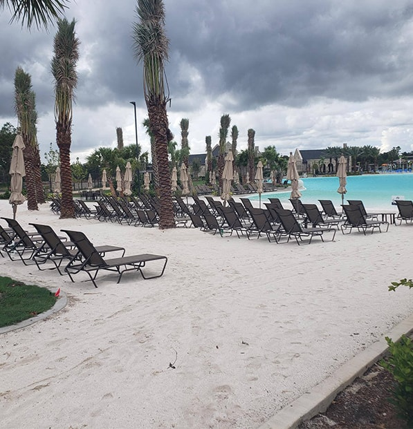 beach chairs on white sand at crystal lagoon
