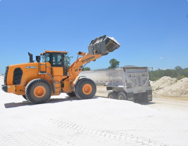 machine dumping sand into truck