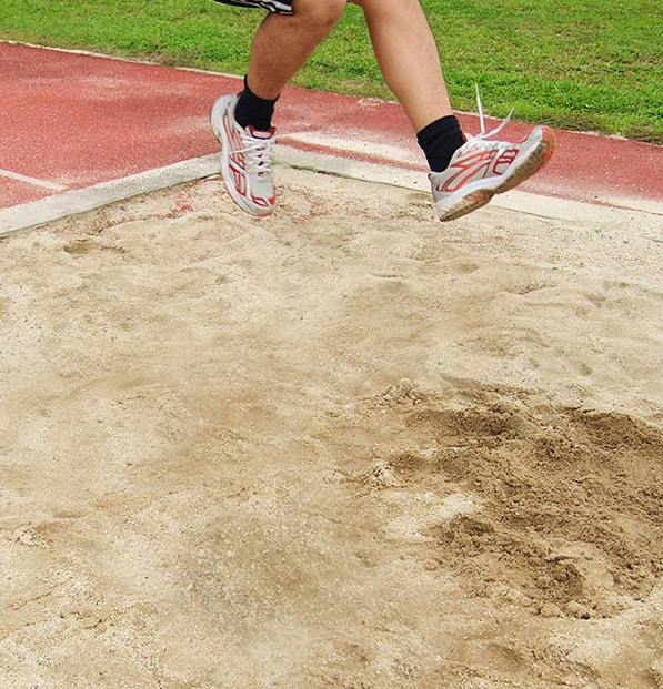 man jumping into long jump sand pit