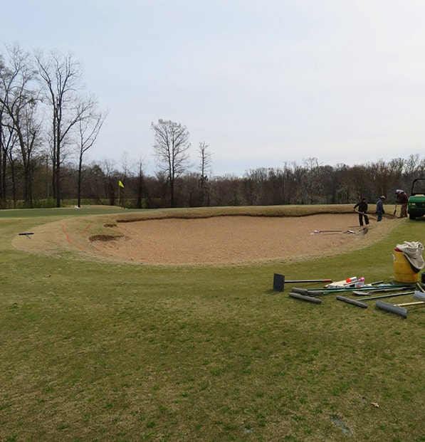 premier play bunker sand being raked at golf course