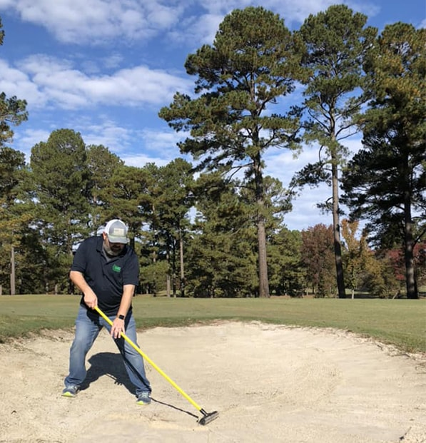 man raking sand in golf course bunker
