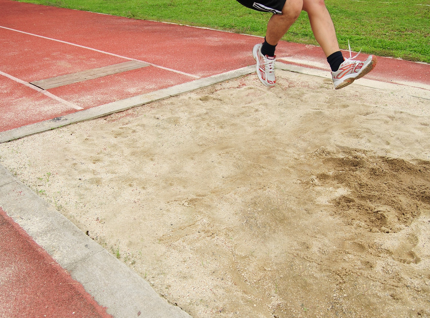 man running and jumping into sand pit